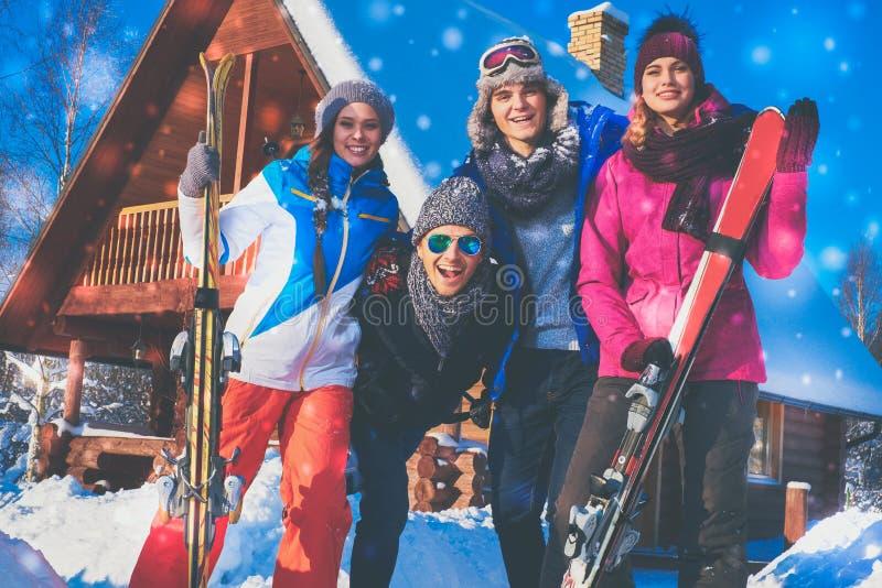 Los amigos pasan vacaciones de invierno en la cabaña de la montaña fotografía de archivo