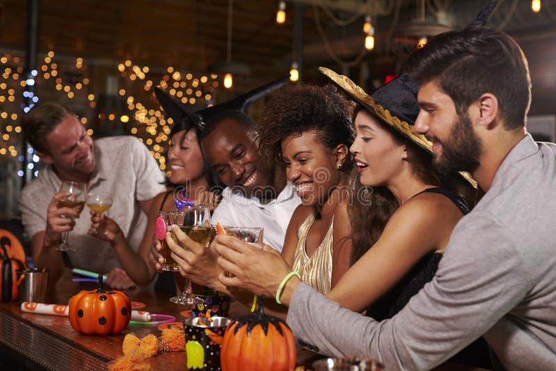 Los amigos que gozan de Halloween van de fiesta en una barra que hace una tostada imagen de archivo libre de regalías
