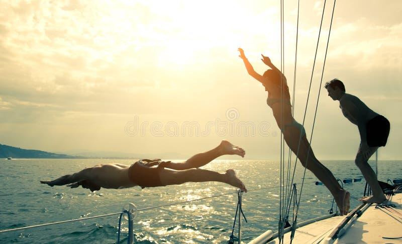 Los amigos que saltan en el agua de un barco de navegación imagen de archivo
