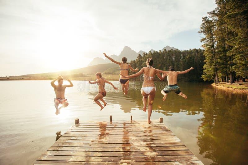 Los amigos que saltan en el agua de un embarcadero fotos de archivo
