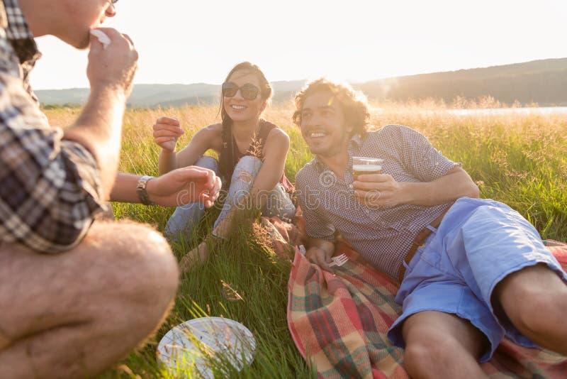 Los amigos que se sientan en hierba y que comen hamburguesas en la barbacoa van de fiesta imágenes de archivo libres de regalías