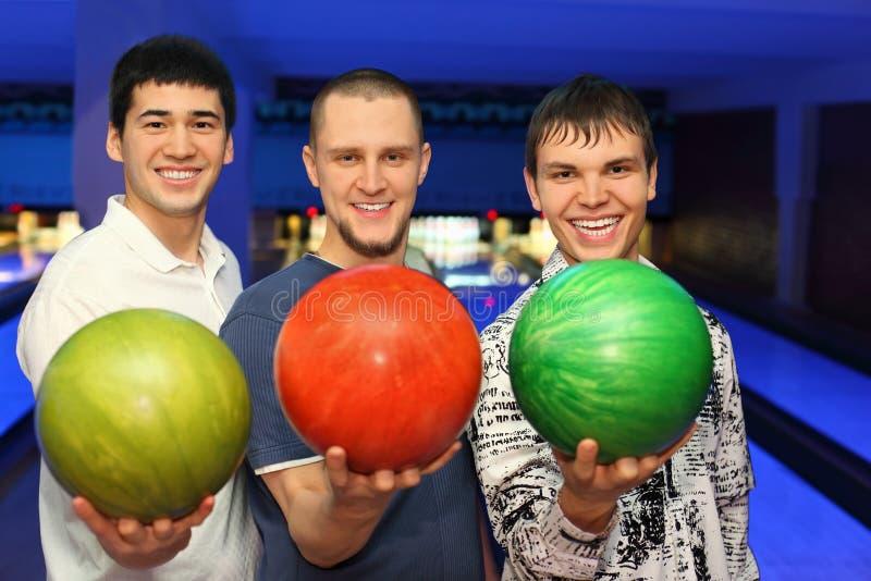 Los amigos se colocan al costado y sostienen las bolas para el bowling imagenes de archivo