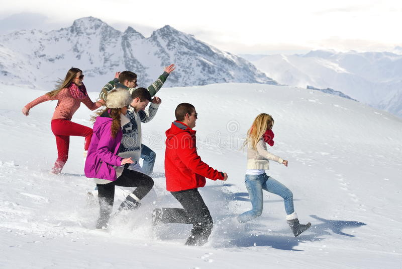Los amigos se divierten en el invierno en nieve fresca fotografía de archivo