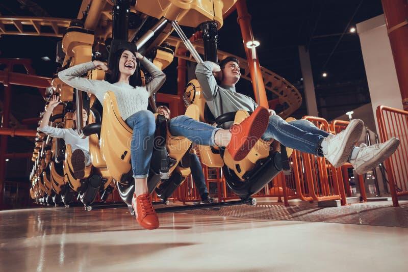 Los amigos se están divirtiendo en parque de atracciones fotografía de archivo