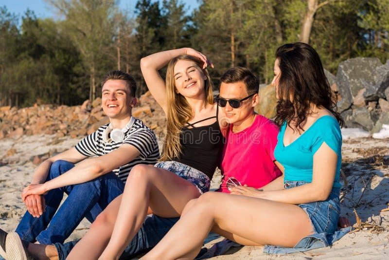 Los amigos se están sentando en la playa en la arena y la risa imagen de archivo
