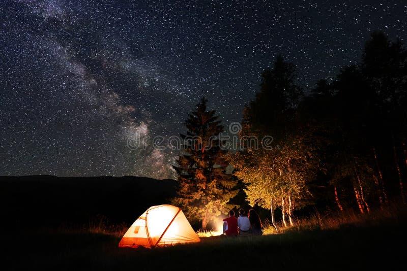 Los amigos se sientan por el fuego en la noche en bosque cerca de la tienda debajo del cielo con el gran número de estrellas y de imágenes de archivo libres de regalías