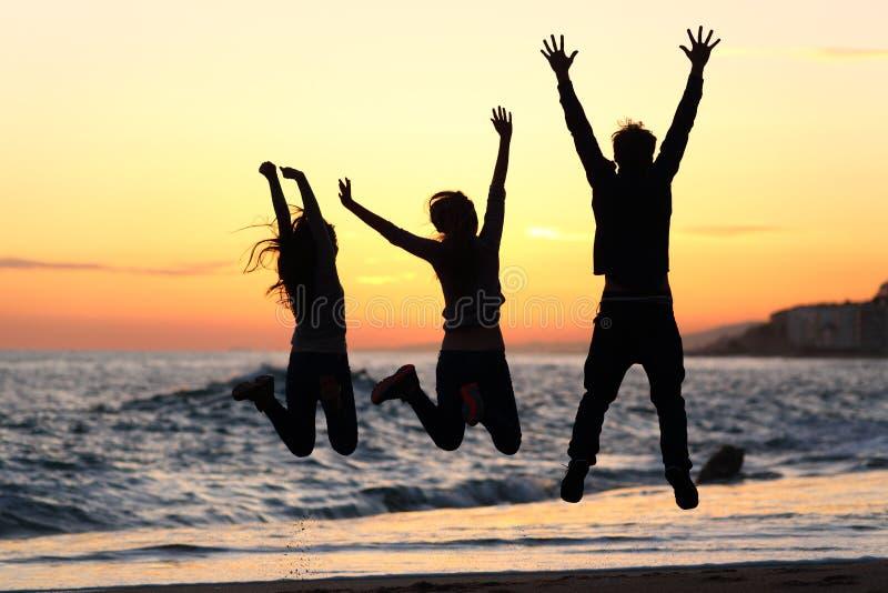Los amigos siluetean el salto feliz en la playa en la puesta del sol foto de archivo libre de regalías