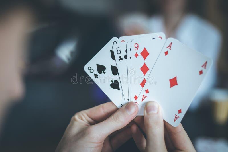 Los amigos son naipes juntos en casa El hombre está sosteniendo las tarjetas en sus manos, mujer en el fondo borroso imágenes de archivo libres de regalías