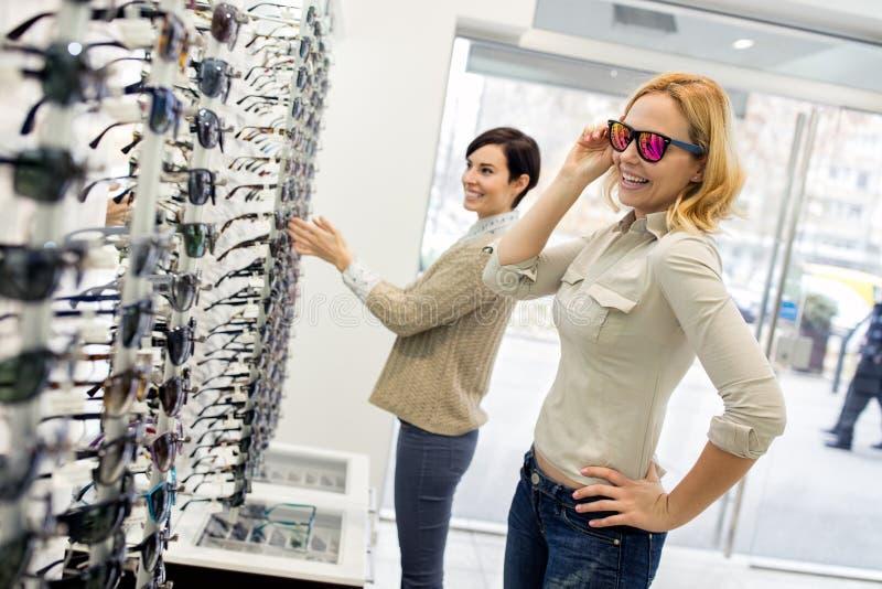 Los amigos sonrientes eligen el marco moderno en tienda imágenes de archivo libres de regalías