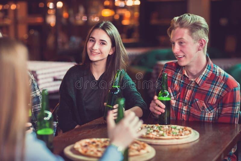 Los amigos teniendo bebidas en una barra, se están sentando en una tabla de madera con las cervezas y la pizza fotos de archivo libres de regalías