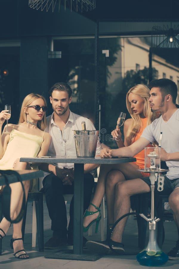 Los amigos vaporizan la cachimba y beben el alcohol en sal?n de la barra foto de archivo libre de regalías