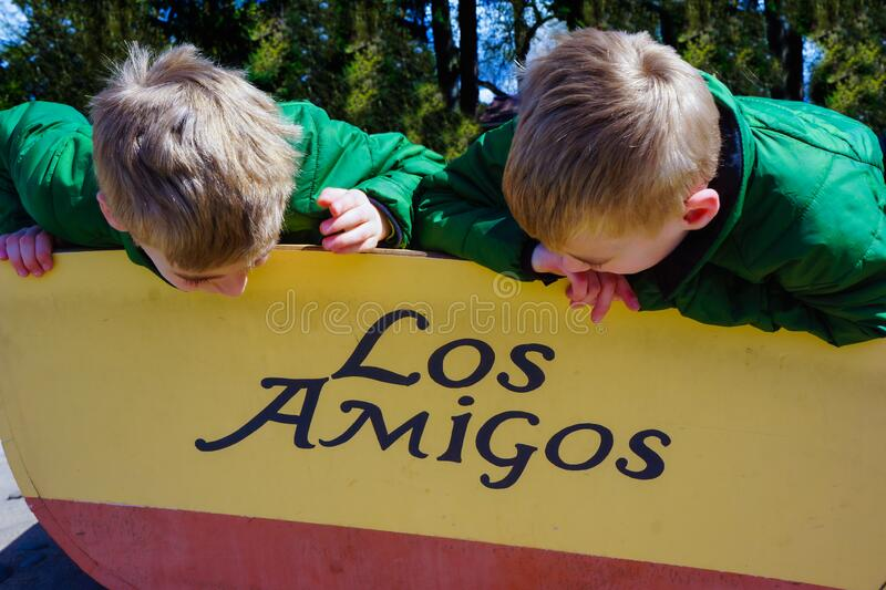 Los Amigos Young Boys are Friends. Twin brothers look at row boat name Los Amigos. Brothers, friends, best buddy stock image