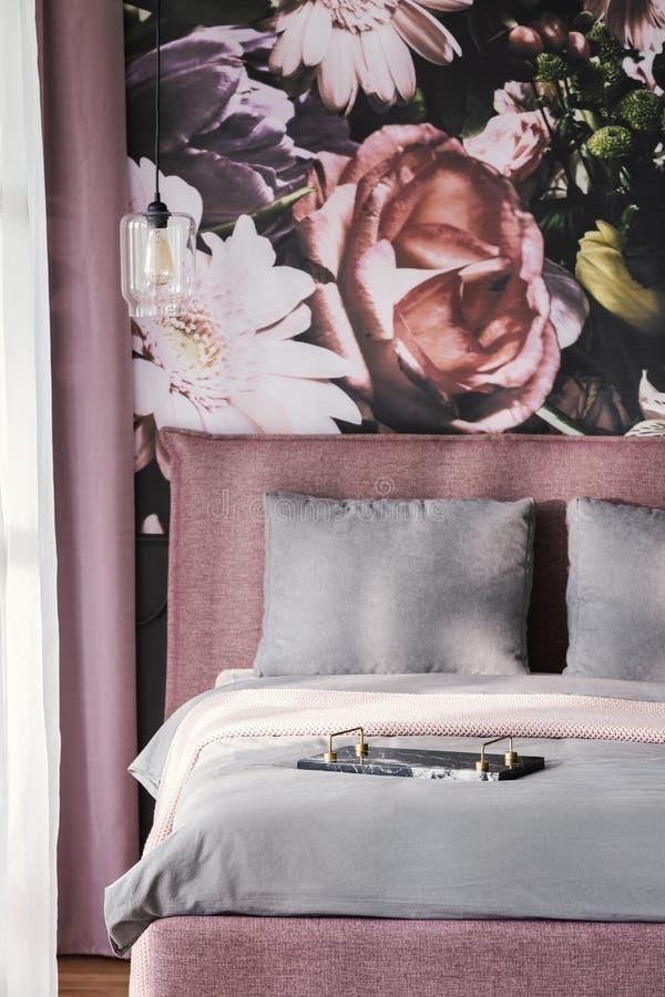 Los amortiguadores grises en cama rosada en interior femenino del dormitorio con las flores wallpaper Foto verdadera foto de archivo