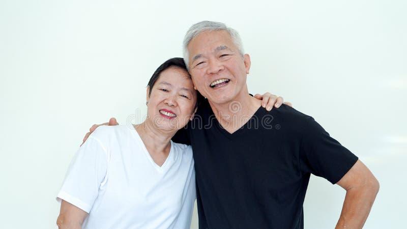 Los ancianos asiáticos brillantes, positivos y felices casaron a la pareja en blanco fotografía de archivo