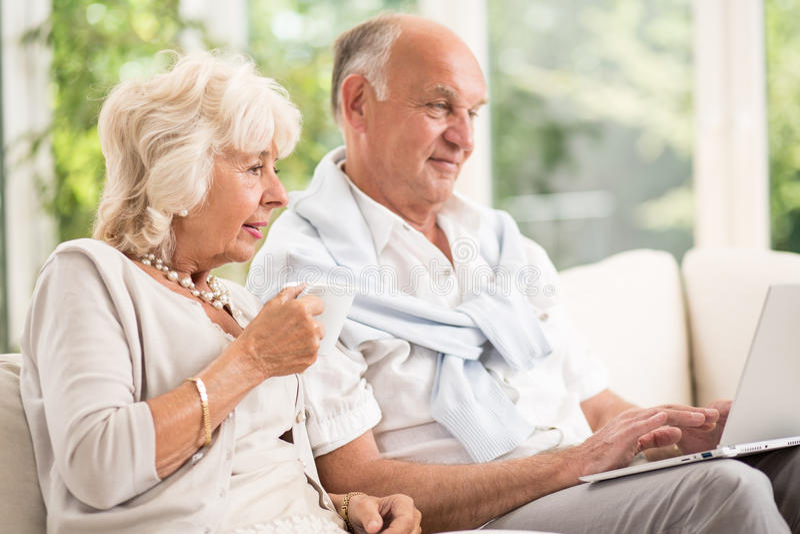 Los ancianos casados se juntan usando el ordenador portátil fotos de archivo