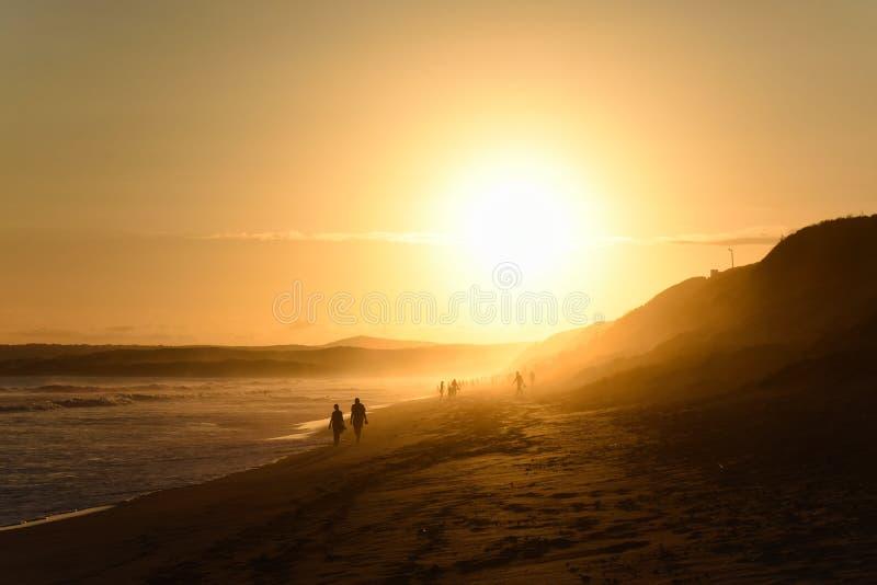 Los ancianos juntan caminar en la playa de la puesta del sol de la tarde imagenes de archivo