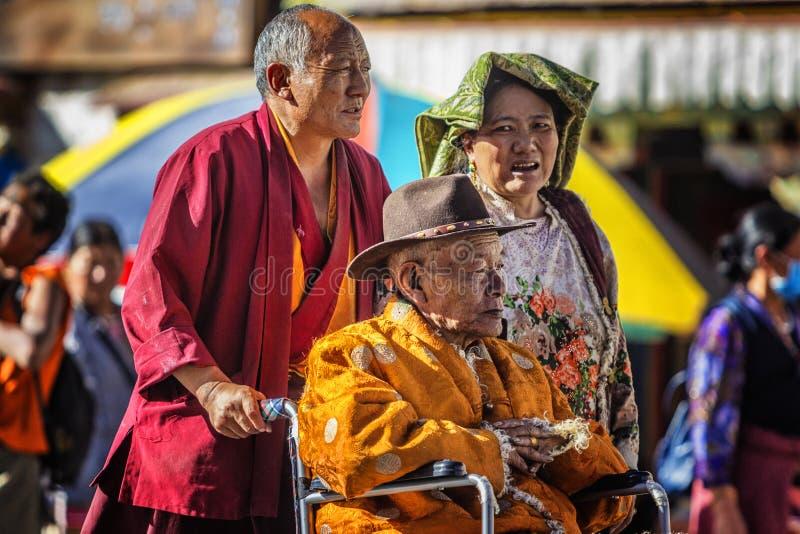 Los ancianos, los monjes y las mujeres en las calles de Tíbet fotografía de archivo