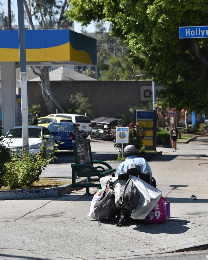Homeless man in a wheelchair. LOS ANGELES, CA/USA - JULY 10, 2019: Homeless man in a wheel chair by a bus stop bench royalty free stock photos