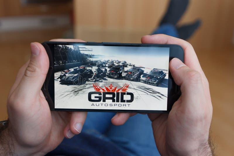 LOS ANGELES, CALIFÓRNIA - 3 DE JUNHO DE 2019: Homem de encontro que guarda um smartphone e o jogo do jogo de Autosport da GRADE n fotografia de stock