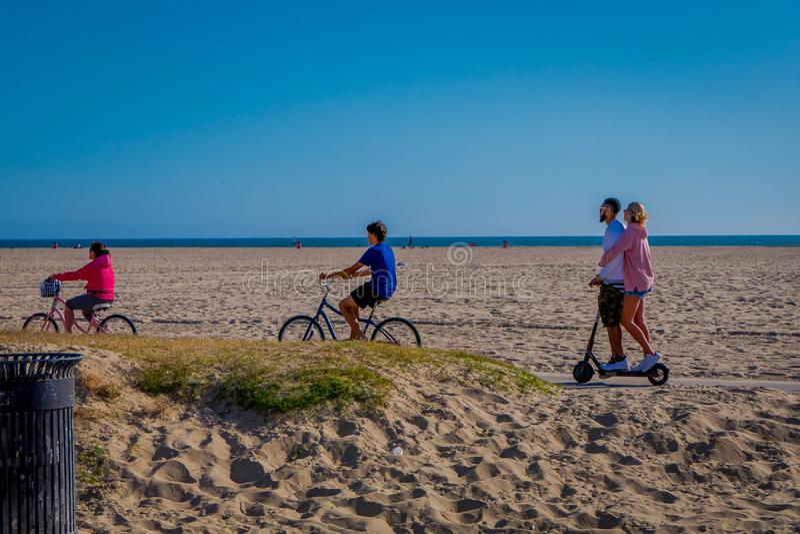 Los Angeles, Califórnia, EUA, JUNHO, 15, 2018: Biking e pares não identificados dos povos em um 'trotinette' na praia de Veneza d fotografia de stock royalty free