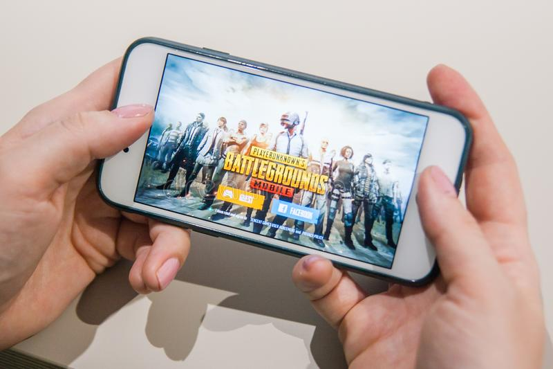 Los Angeles, Californië, de V.S. - 25 Februari 2019: Handen die een smartphone met PUBG-de Slagveldenspel van Spelerunknowns houd stock foto