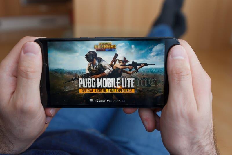 LOS ANGELES, CALIFORNIË - JUNI 3, 2019: Het liggen Mens die een smartphone houden en het spelen van de Slagvelden Lite PUBG van P stock afbeelding