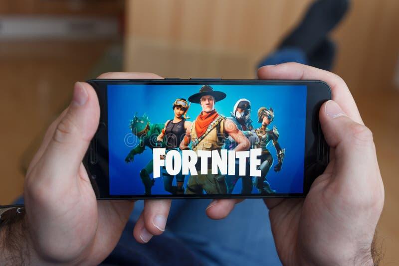 LOS ANGELES, CALIFORNIA - 3 DE JUNIO DE 2019: Hombre de mentira que lleva a cabo un smartphone y jugar al juego de Fortnite en la foto de archivo