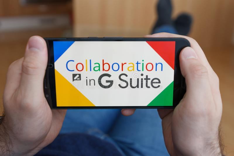 LOS ANGELES, CALIFORNIA - JUNE 3, 2019: Close up to male hands holding smartphone using G Suite application collaboration. An royalty free stock photography