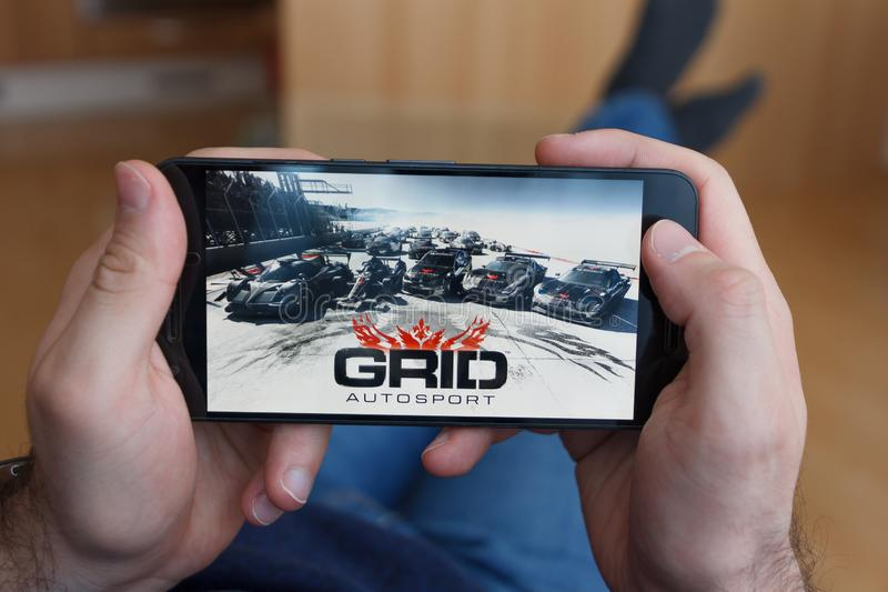 LOS ANGELES, CALIFORNIA - JUNE 3, 2019: Lying Man holding a smartphone and playing the GRID Autosport game on the smartphone. Screen. An illustrative editorial stock photography