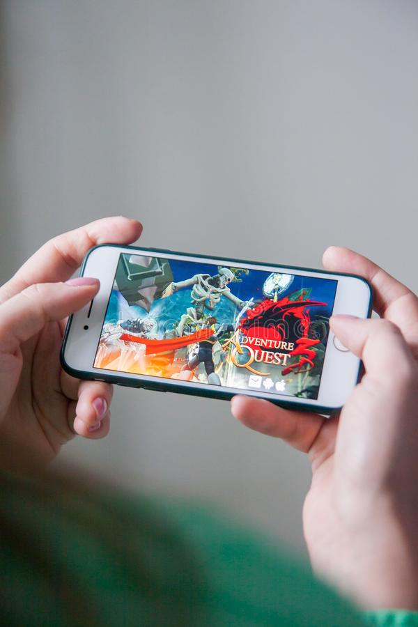 Los Angeles, California, USA - 25 February 2019: Hands holding a smartphone with Adventure Quest game on display screen stock photography
