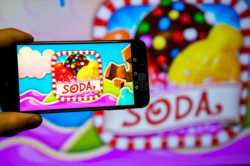 Los Angeles, California, USA - 21 February 2019: Hands holding a smartphone with CANDY CRUSH SAGA game against the big screen.  stock photos