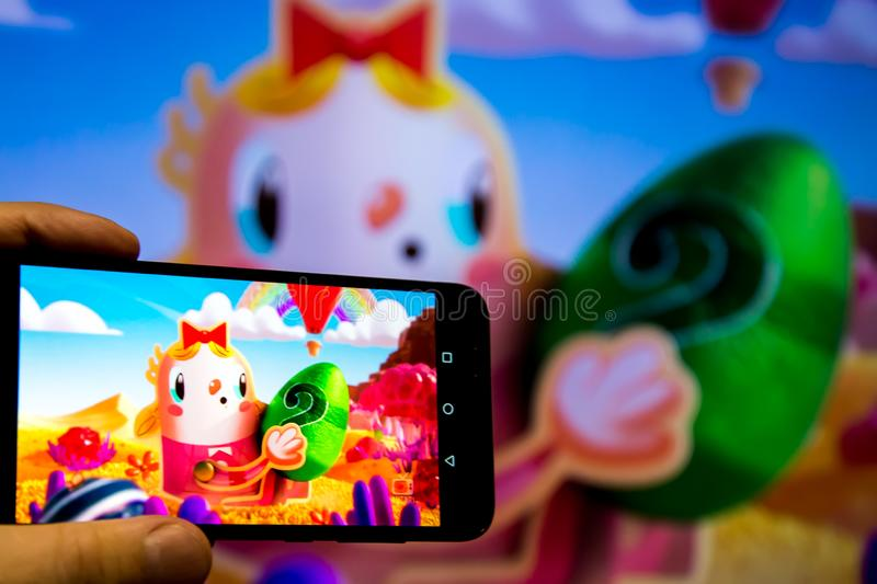 Los Angeles, California, USA - 21 February 2019: Hands holding a smartphone with CANDY CRUSH SAGA game against the big screen.  stock photo
