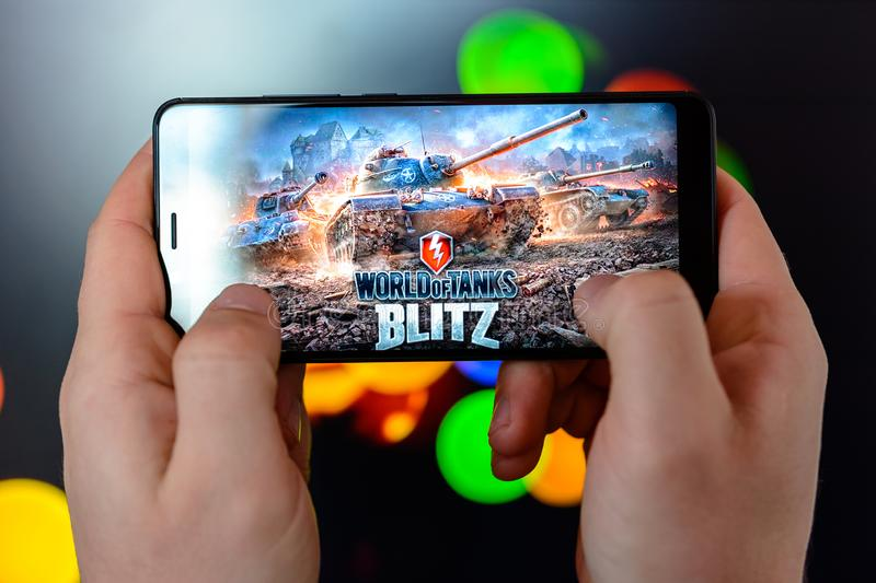 Los Angeles, California, USA - 9 March 2019: The man holds the smartphone close-up in his hands and plays the world of tanks blitz stock images