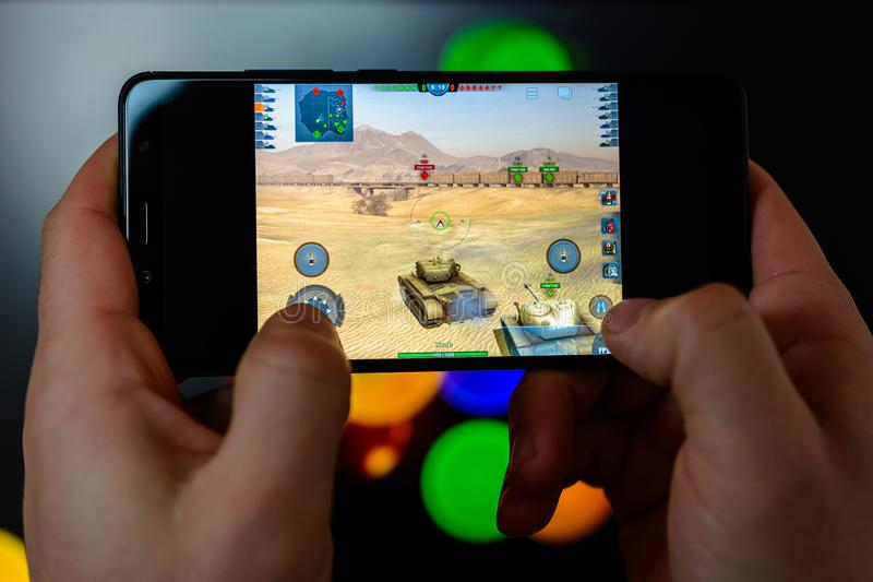 Los Angeles, California, USA - 9 March 2019: The man holds the smartphone close-up in his hands and plays the world of tanks blitz royalty free stock image