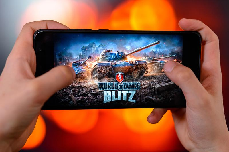 Los Angeles, California, USA - 9 March 2019: The man holds the smartphone close-up in his hands and plays the world of tanks blitz stock photo