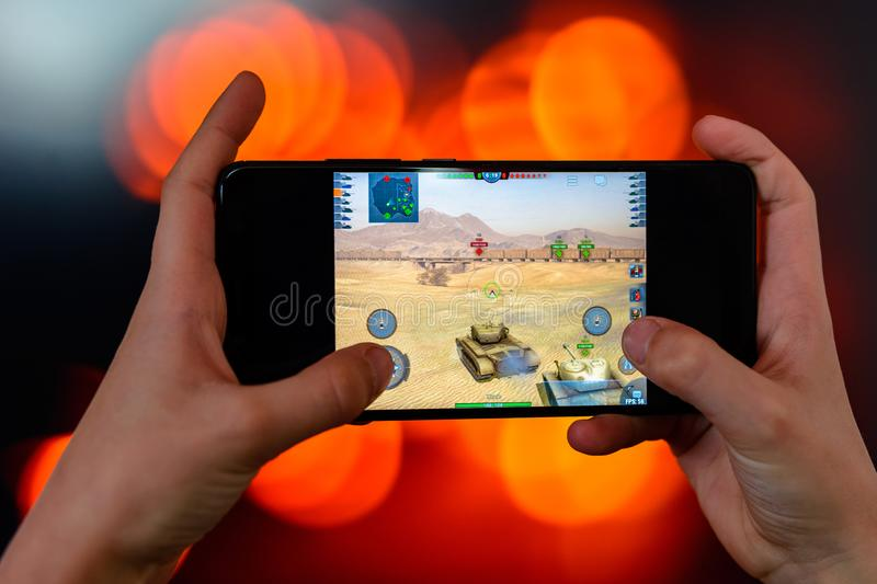 Los Angeles, California, USA - 9 March 2019: The man holds the smartphone close-up in his hands and plays the world of tanks blitz stock image
