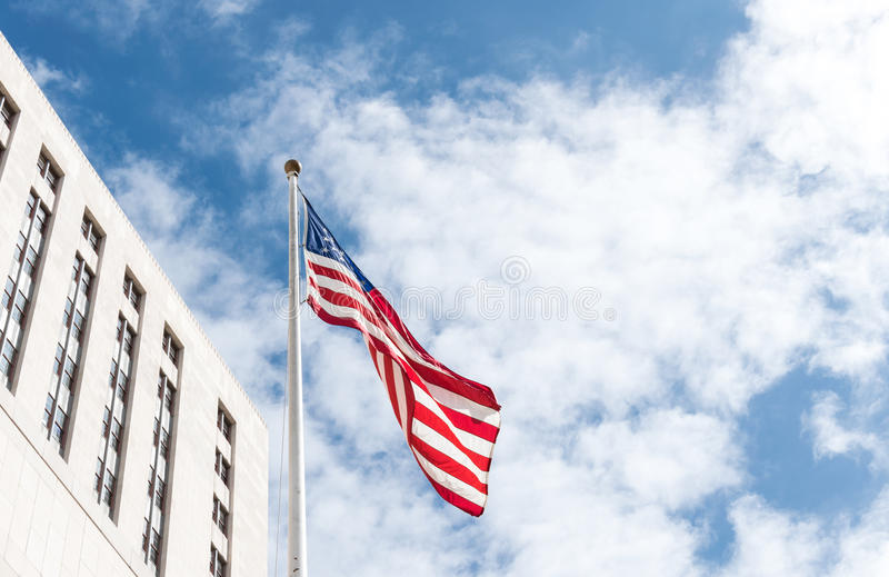 Los Angeles, City Hall and American flag against the blue sky stock images