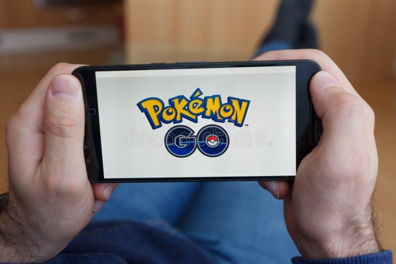 LOS ANGELES KALIFORNIA, CZERWIEC, - 3, 2019: Łgarski mężczyzna trzyma smartphone i bawić się Pokemon Iść gra na smartphone ekrani obraz royalty free