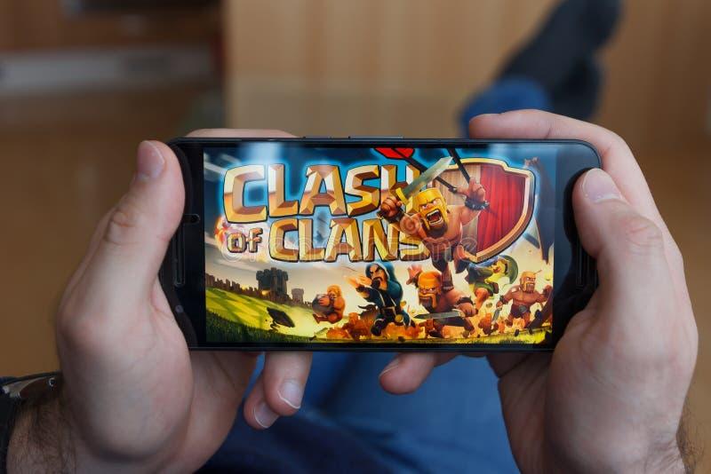 LOS ANGELES KALIFORNIA, CZERWIEC, - 3, 2019: Łgarski mężczyzna trzyma smartphone i porównuje zderzenie klanów i Fortnite gry na obrazy royalty free