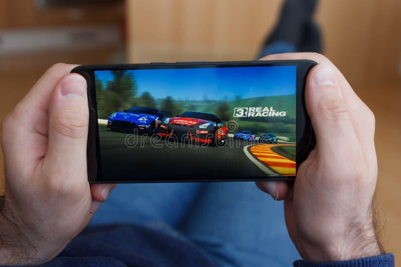 LOS ANGELES KALIFORNIEN - JUNI 3, 2019: Liggande man som rymmer en smartphone och att spela leken för Real Racing 3 på smartphone royaltyfri fotografi