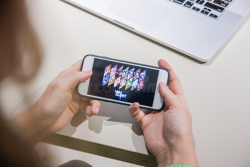 Los Angeles Kalifornien, USA - 25 Februari 2019: Händer som rymmer en smartphone med leken för inbilskhet MOBA på skärmskärmen royaltyfri fotografi