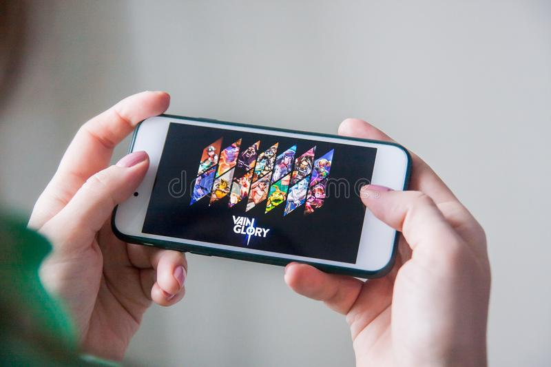 Los Angeles Kalifornien, USA - 25 Februari 2019: Händer som rymmer en smartphone med leken för inbilskhet MOBA på skärmskärmen fotografering för bildbyråer