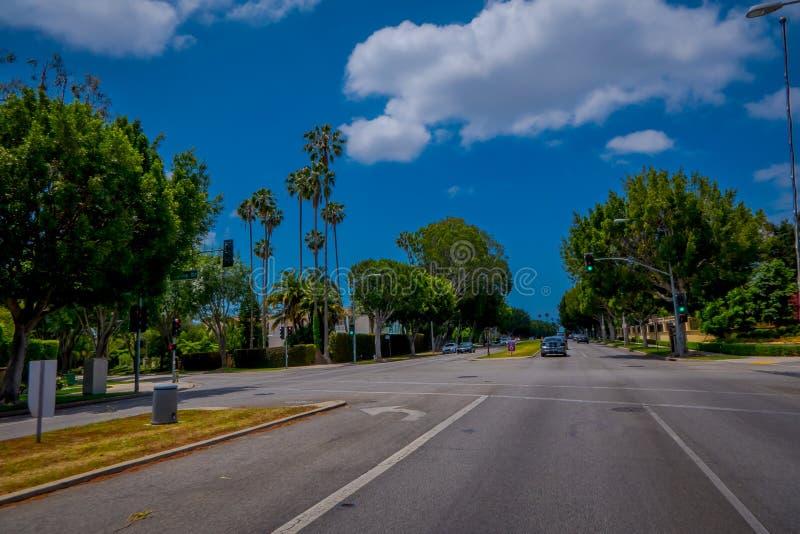 Los Angeles Kalifornien, USA, JUNI, 15, 2018: Palmträdgata i Beverly Hills och bilar som cirkulerar i vägarna av arkivbilder