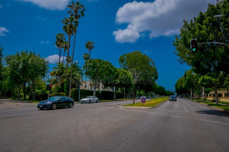 Los Angeles Kalifornien, USA, JUNI, 15, 2018: Palmträdgata i Beverly Hills och bilar som cirkulerar i vägarna av royaltyfri fotografi