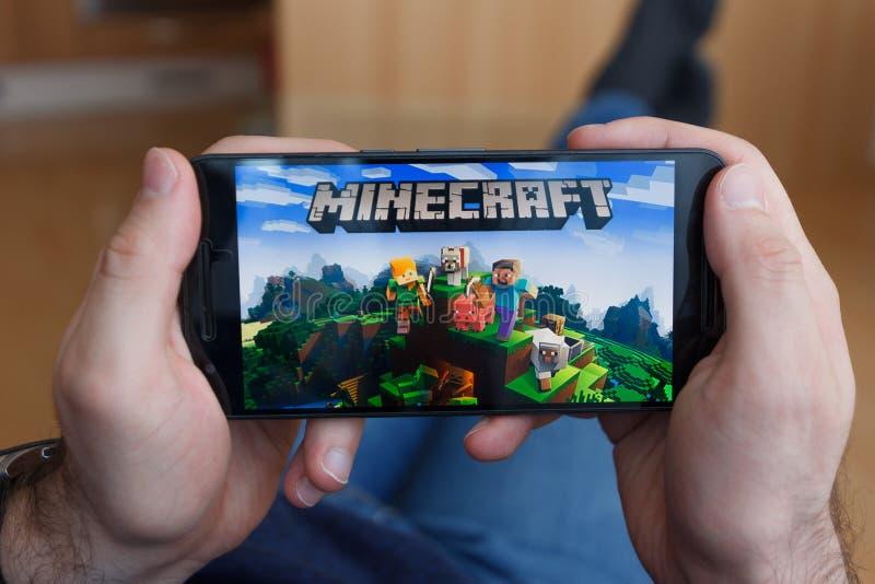 LOS ANGELES, LA CALIFORNIE - 3 JUIN 2019 : Homme menteur tenant un smartphone et jouer le jeu de Minecraft sur l'écran de smartph image libre de droits