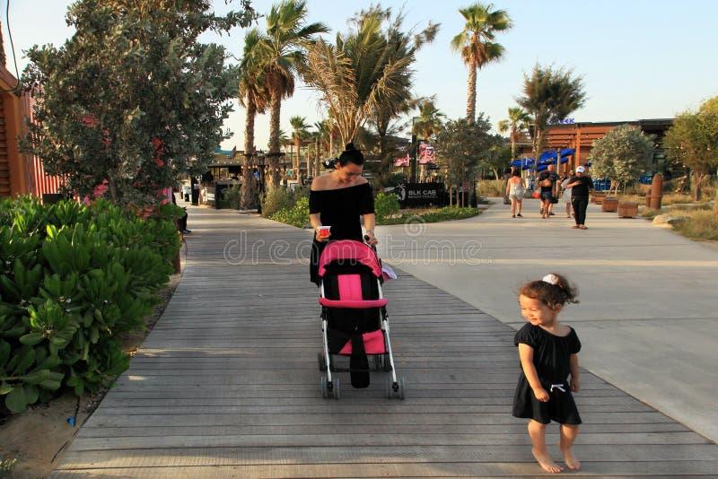 Los Angeles Mer w Dubaj, UAE - Maj 06, 2018: Kobieta z dzieckiem chodzi wzdłuż deptaka na losu angeles Mera ` s plaży Los Angeles obrazy royalty free