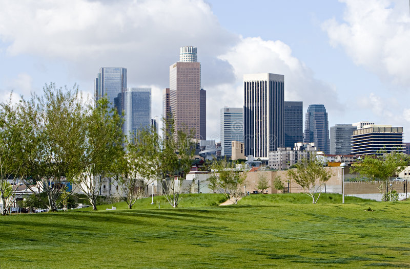Los Angeles Skyline From Park. Los Angeles skyline against blue sky with clouds from city park stock photo