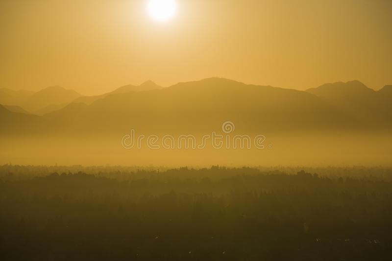 Los Angeles Smoggy Summer Sun. Hot smoggy summer sun rising above the San Fernando Valley and San Gabriel Mountains in Los Angeles, California stock photo