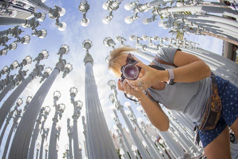 LOS ANGELES USA - April 2018: En gladlynt rolig turist- flicka som tar foto med en kamera på det berömda konstverket Urban arkivfoto