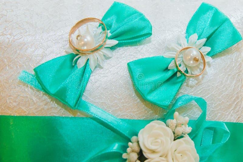 Los anillos de bodas están en una almohada blanca y sadely el ramo de la novia imagen de archivo